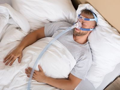 Man with a CPAP machine in bed