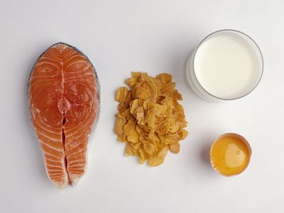 Foods with vitamin D, including fatty fish, cereal, milk, and orange juice are displayed on a white background.