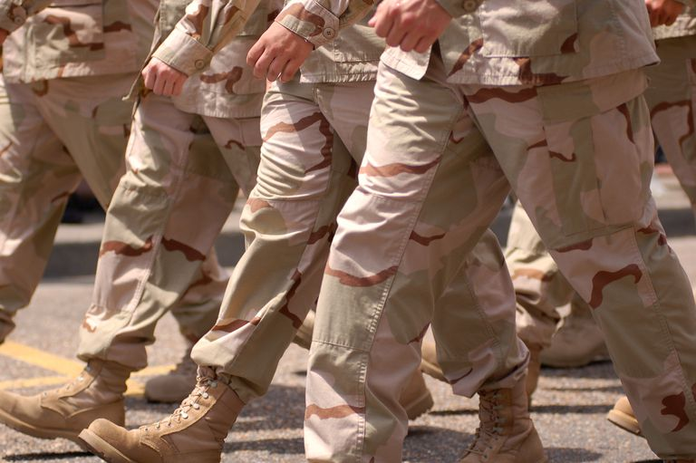 Close up of the legs and feet of Gulf War soldiers marching.