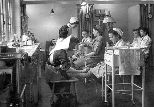 An old hospital where a nurse is bandaging a woman's leg