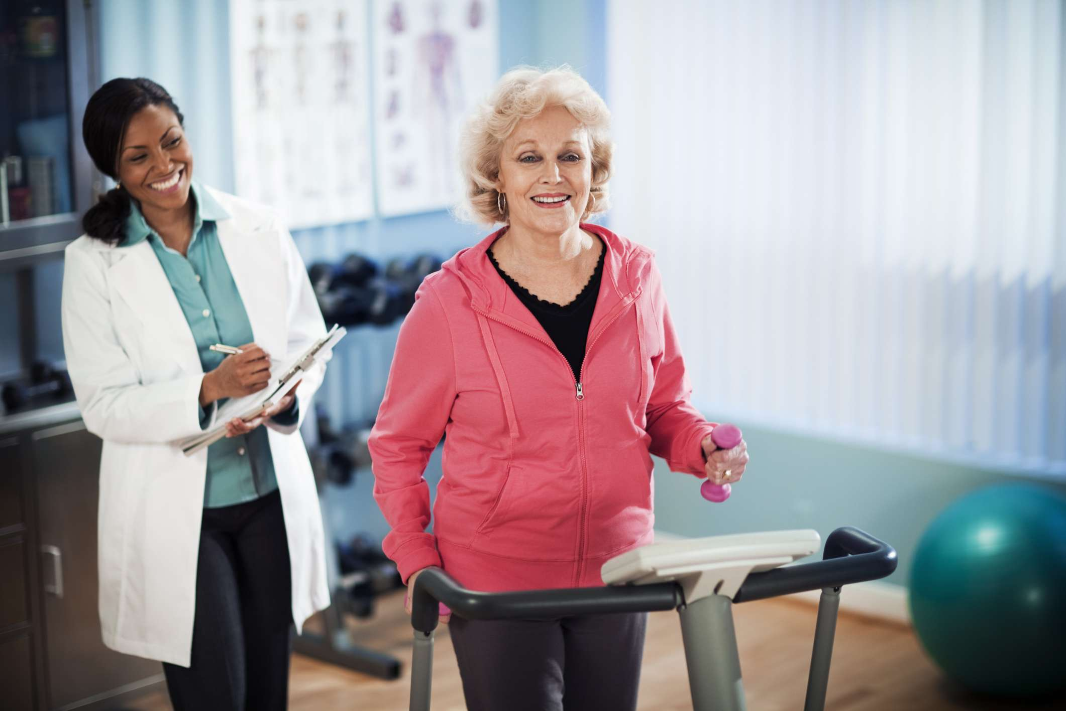 Older woman walking on treadmill with doctor next to her