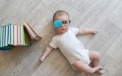 Baby wearing glasses with one lens covered. Eye patching is one way to treat lazy eye