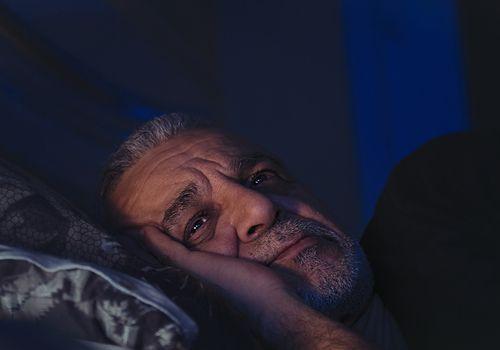 Man awake at night in bed