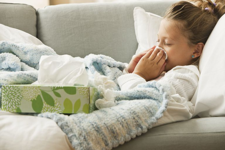 Caucasian girl laying on couch blowing her nose - stock photo