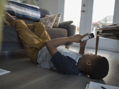 Teenage boy laying, using cell phone on living room sofa
