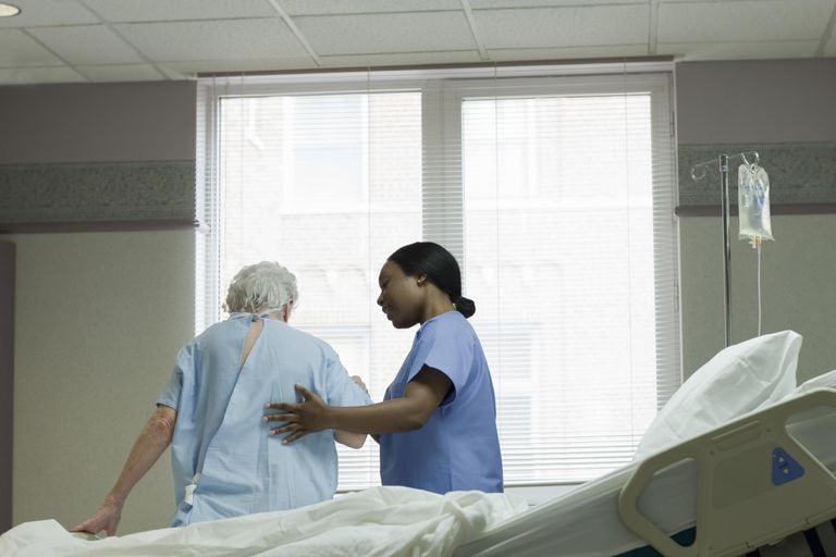 African American nurse helping patient stand up