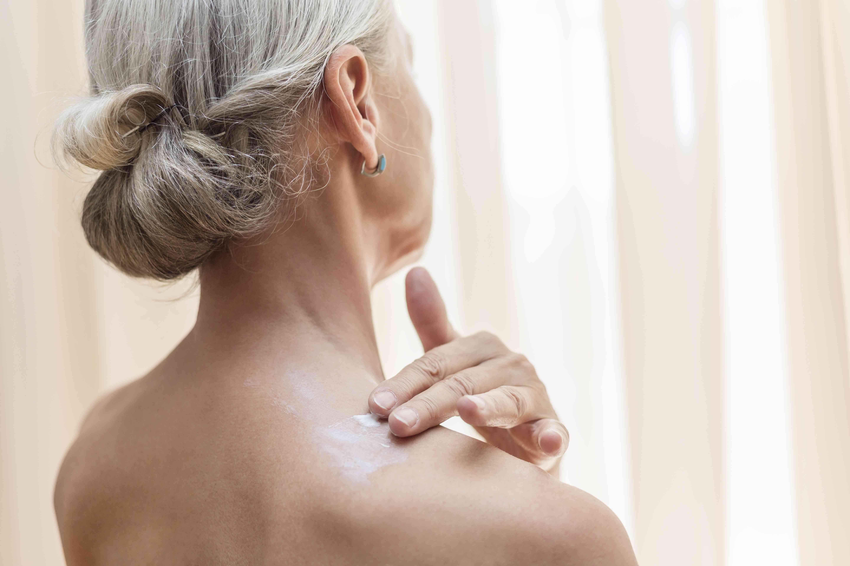 Back view of senior woman applying cream on neck