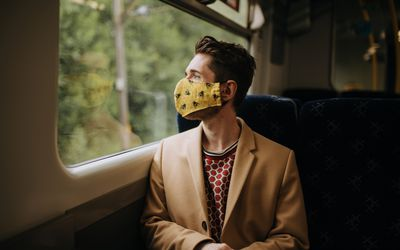 young man wearing face mask traveling by train