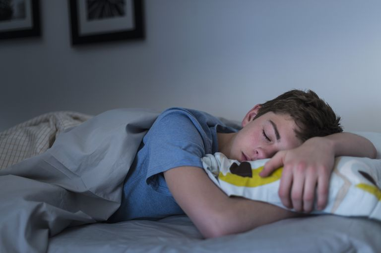 Teen boy asleep in bed