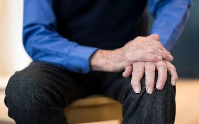 A man with Parkinson's disease holds his knee