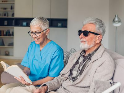 Woman reading to man with vision loss
