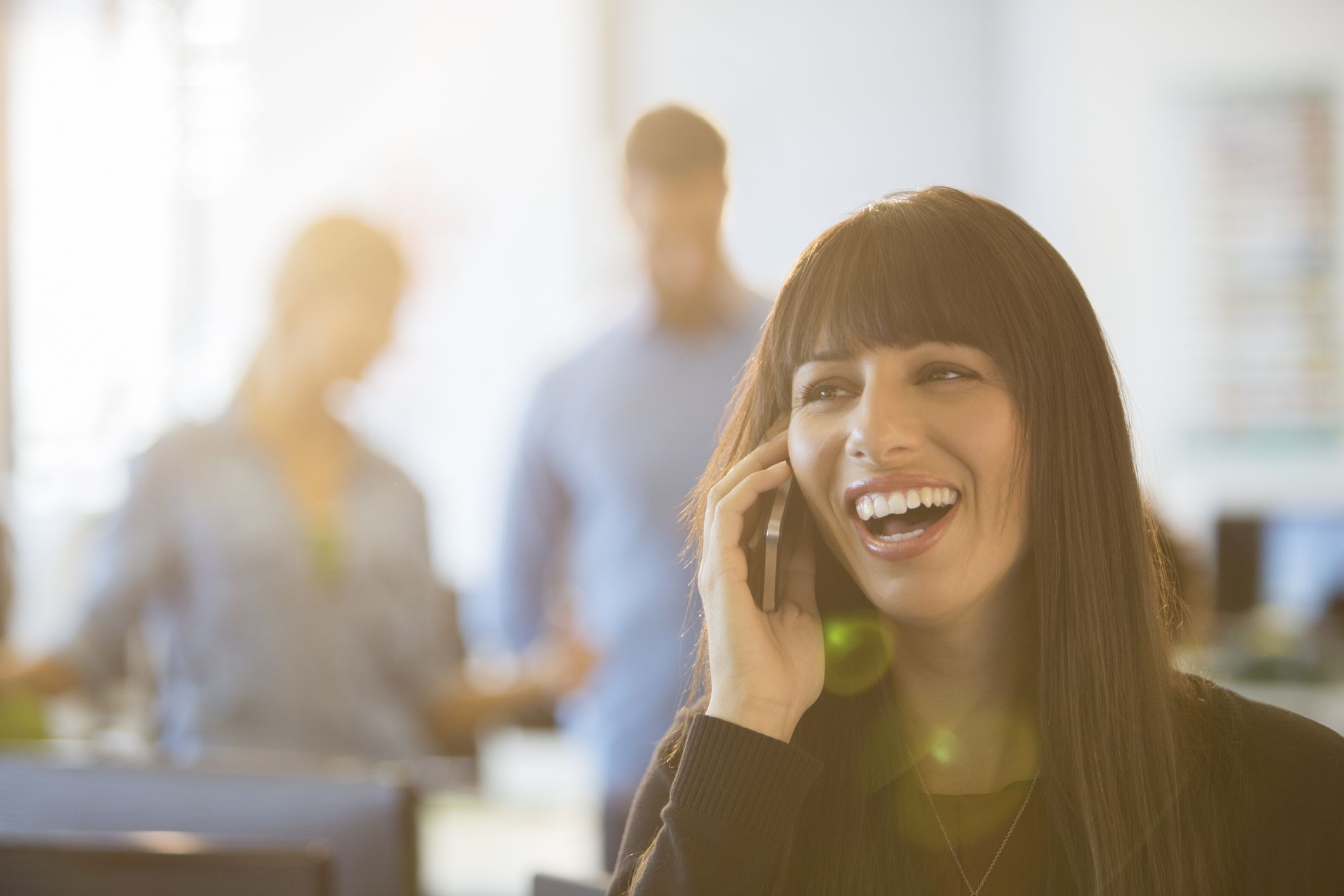 Woman with a big smile talking on the phone