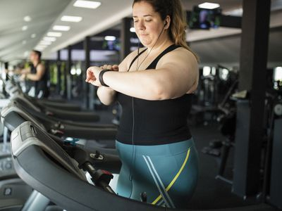Woman checking smartwatch while on a treadmill