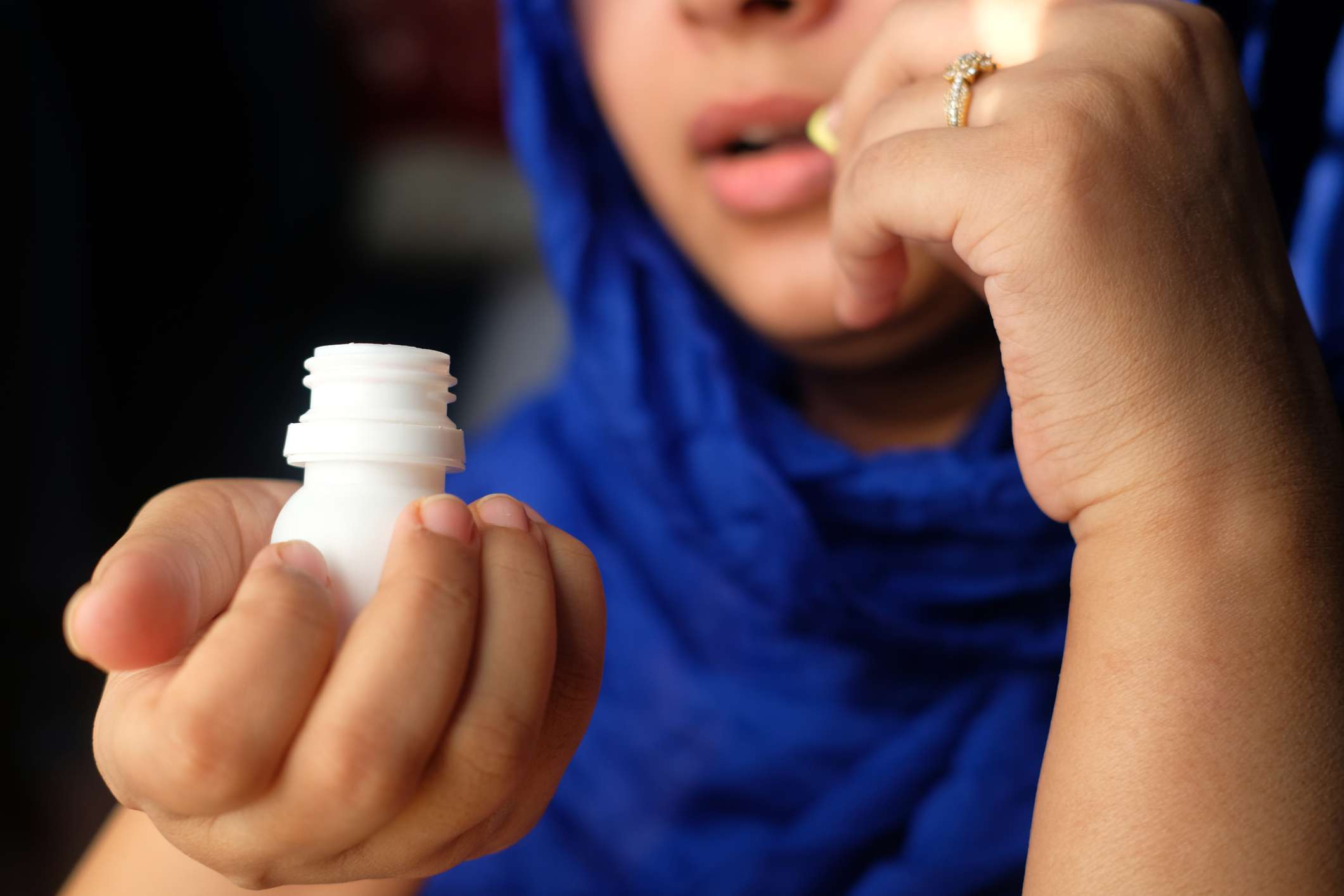 Woman wearing a head scarf holding a pill bottle and taking a pill