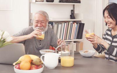 older couple drinking orange juice at breakfast table
