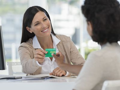 Receptionist giving insurance card to patient.