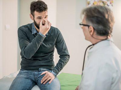 Man describing symptoms to his doctor