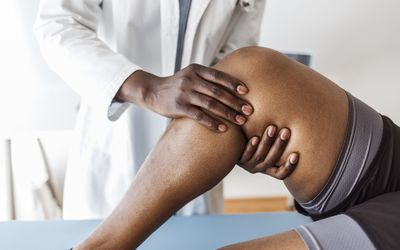 Doctor consulting with patient who has knee problems.