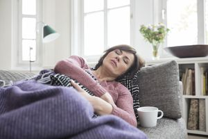 Woman laying on the couch with stomach pain