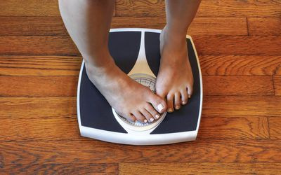 Woman standing on a bathroom scale, covering the numbers with her foot
