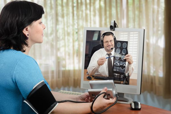 A woman having a telemedicine consult with her doctor via computer