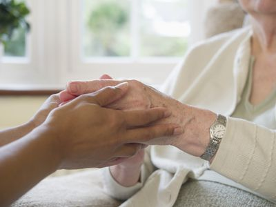 A caregiver holding the hand of a patient