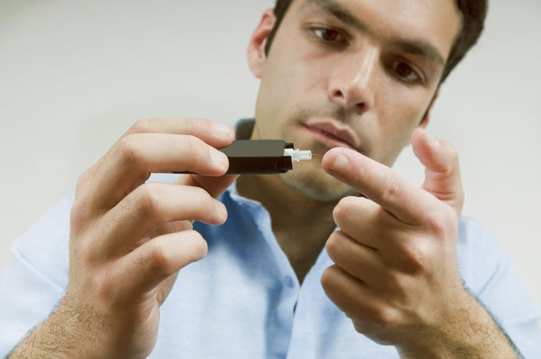 man testing blood sugar