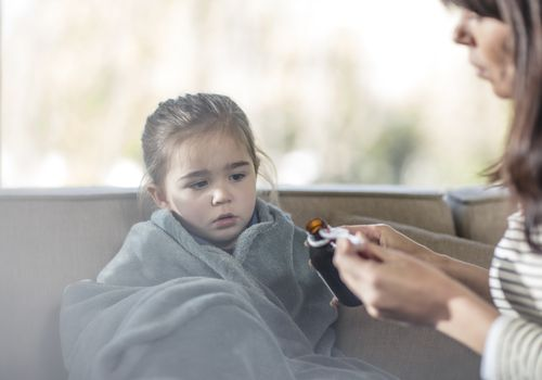 Mother pouring medicine for daughter wrapped in blanket on sofa