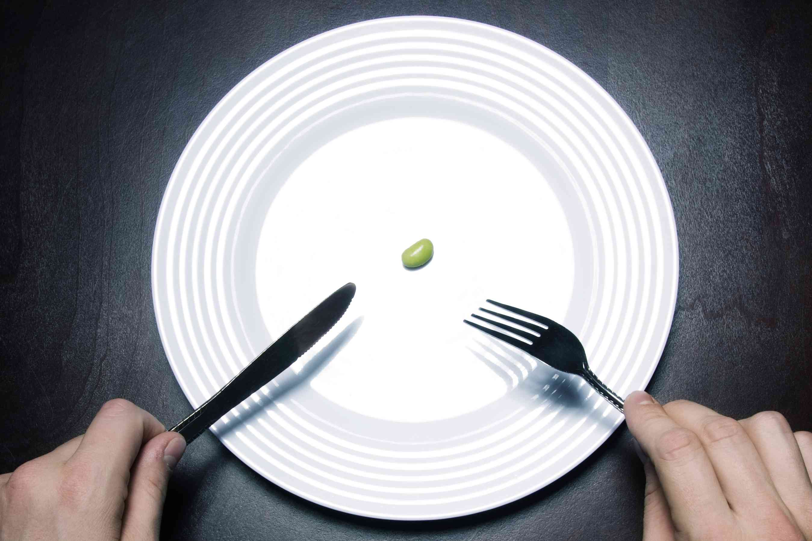 One bean on an otherwise empty white plate