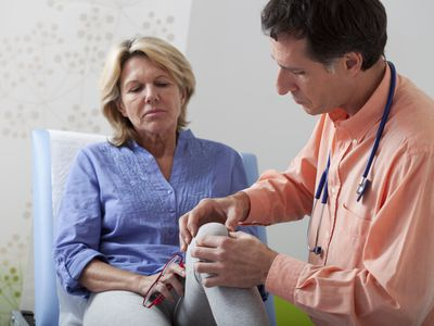 doctor evaluating senior woman's knee