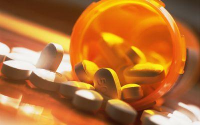 Prescription pills spilling out of pill bottle, close-up