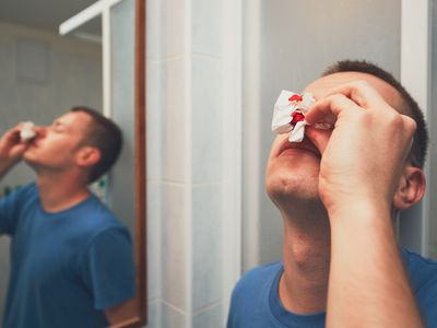 A man in the bathroom with a bloody nose