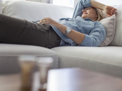 A woman on the couch suffering from a headache