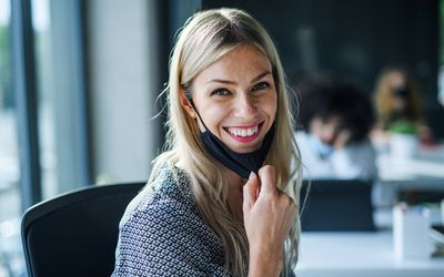 woman in office pulling down mask