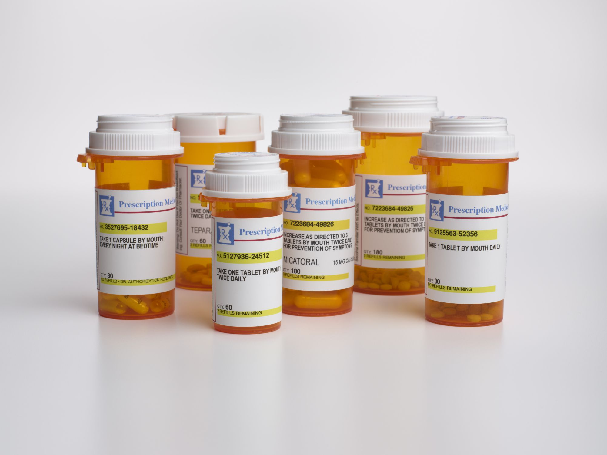 Pill bottles grouped together on a white surface against a white background