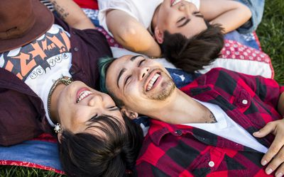 Teenagers lying in the grass, laughing