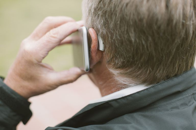 elderly man using cell phone with hearing aid
