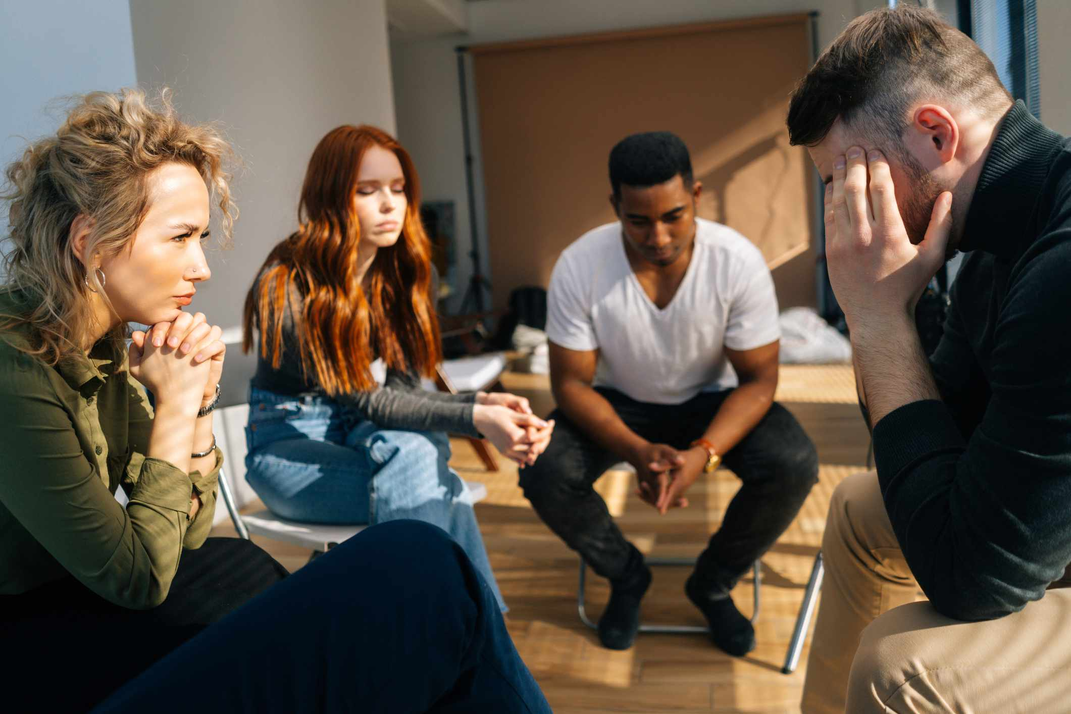 Two men and two women seated in a circle having an intense emotional conversation
