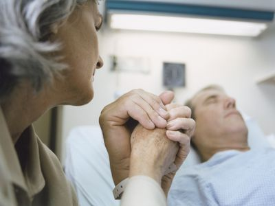 Old man in hospital bed holding hands with woman