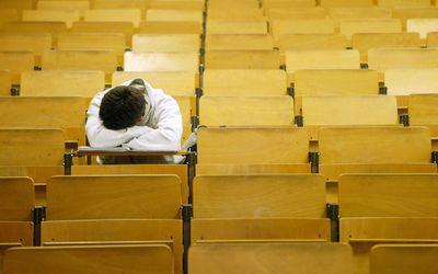 Kid sleeping with head on desk in auditorium
