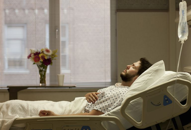 Man in hospital bed holding his side