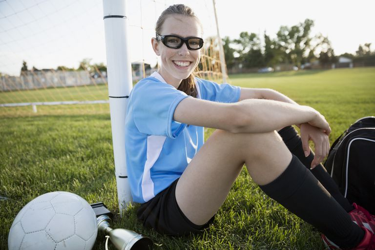 Portrait smiling middle school girl soccer player leaning on goal net post