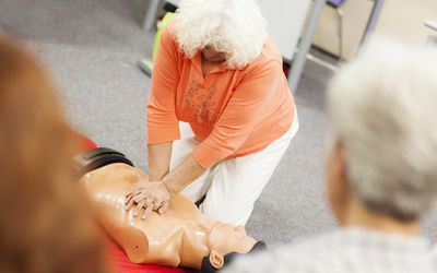 woman practicing CPR on dummy