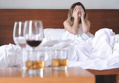 Woman in bed with a headache with glasses of alcohol blurry in the foreground.