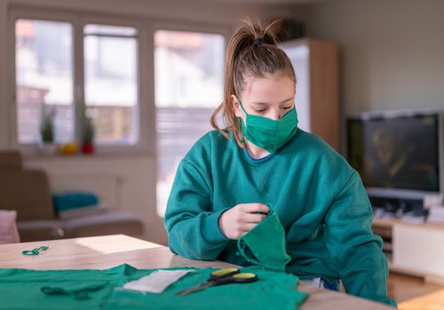 young woman cutting a face mask from a t-shirt