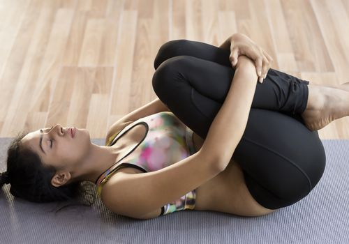 Woman knees to chest on mat