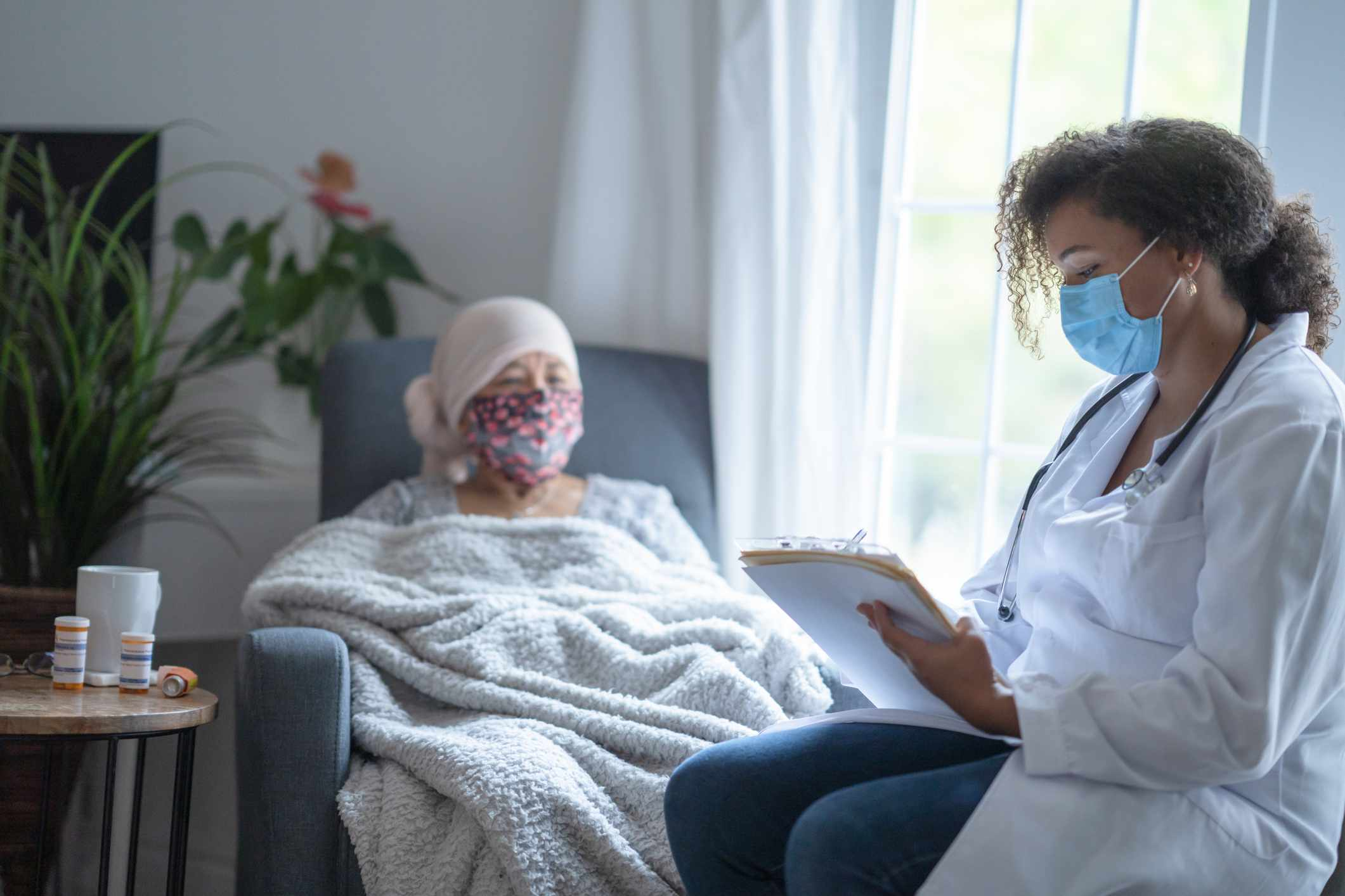 Senior asian female cancer patient wearing mask talking to doctor - stock photo