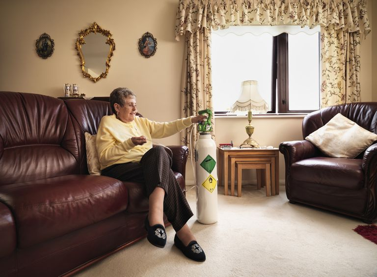Senior woman using oxygen tank on the couch