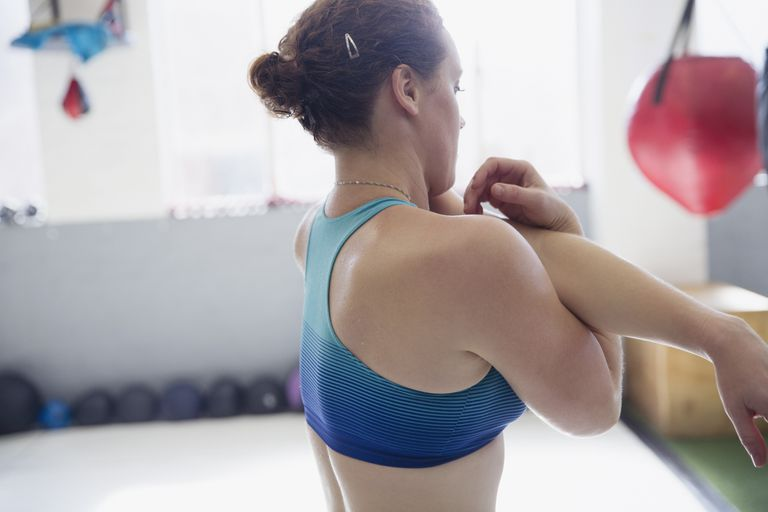 Woman in a gym stretching her arm and shoulder