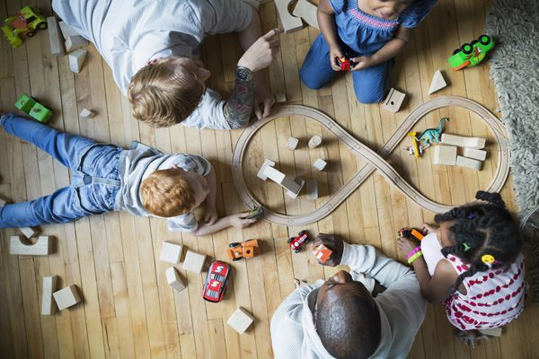 Overhead view fathers and children enjoying play date playing with toy train and wood blocks